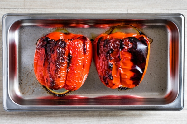 Two roasted red bell peppers in a stainless steel oven pan, fresh from the oven with blackened skin