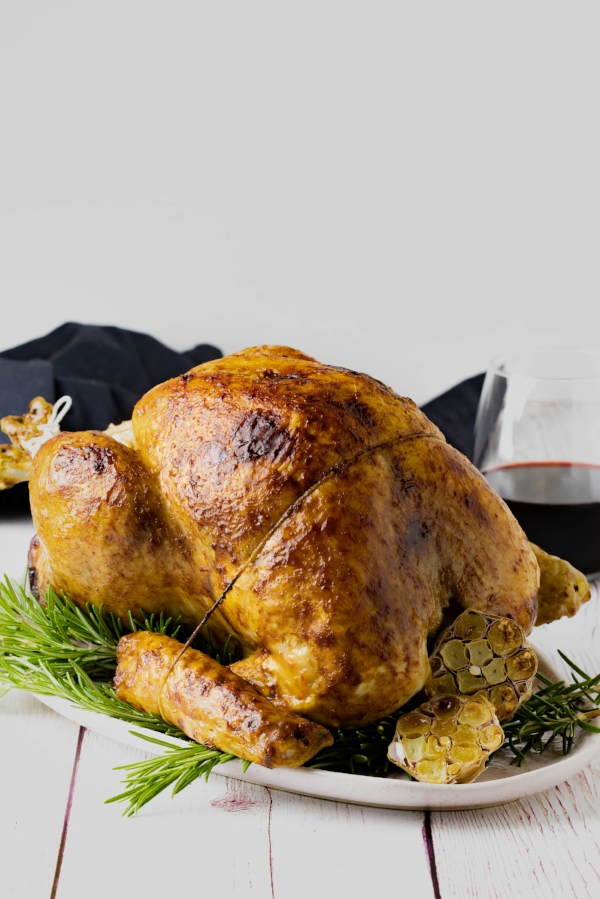 A whole turkey, cooked in a steam oven, presented on a bed of rosemary with roasted garlic to the side, and a glass of red wine in the background.
