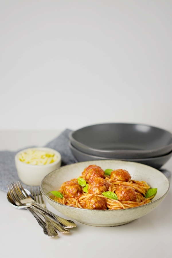 Oven baked meatballs with spaghetti and basil leaves, served in a wide stone coloured bowl with cutlery and shredded cheese next to it.