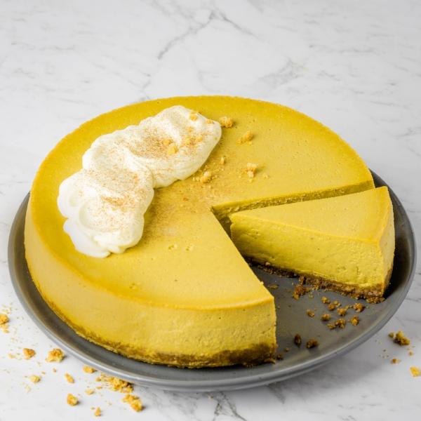 Steamed pumpkin cheesecake, served whole with a single wedge cut out, with mascarpone cheese dolloped over the top.
