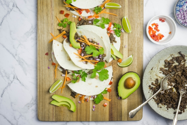 Soft tortilla tacos filled with shredded beef cheeks and vegetables, with cilantro, avocado and lime scattered around the wooden serving board.
