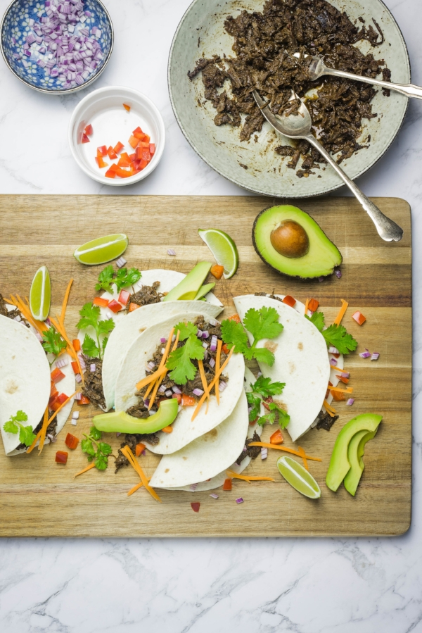 Shredded beef cheek tacos made with soft flour tortillas, fresh vegetables, lime wedges and slices of avocado, served on a rustic wooden board.