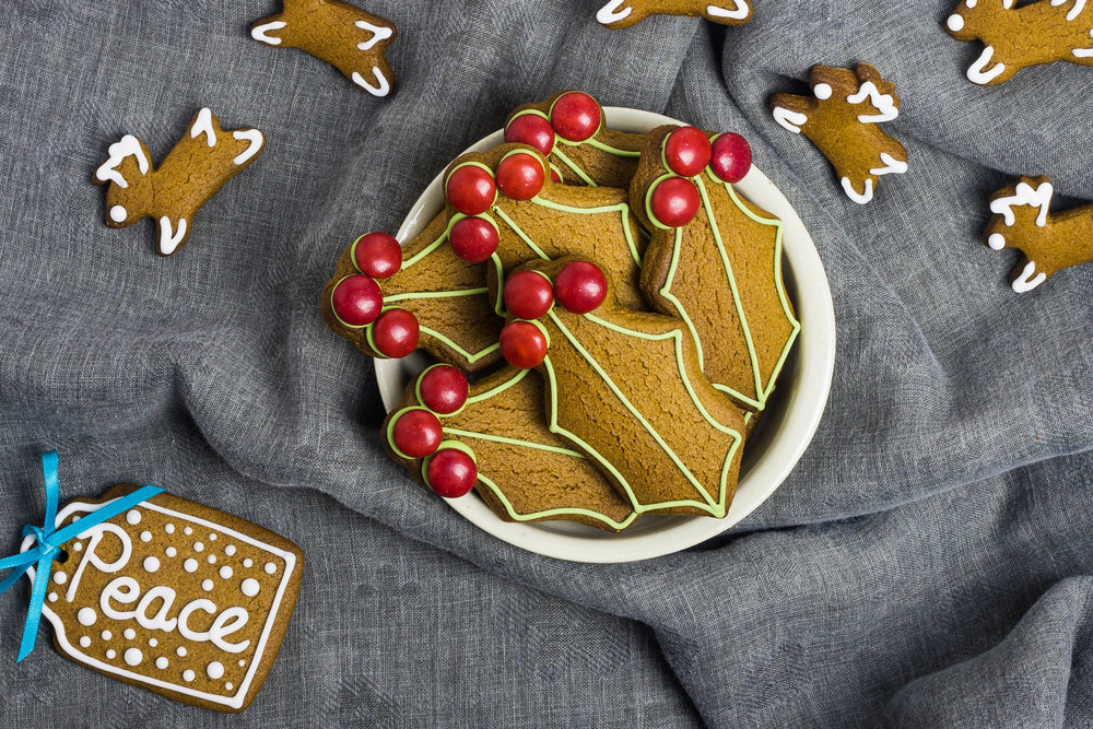 Decorated gingerbread cookies in holly shapes, reindeer and edible gift tags with 'peace' written on in royal icing.