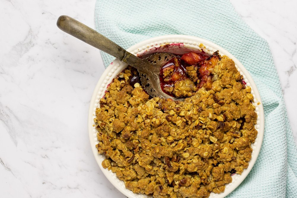 Healthy fruit crumble, made with plums, served in a round white dish with a spoonful removed to show the filling.