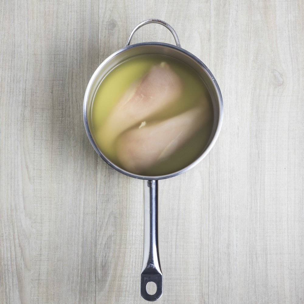 Raw chicken breasts and chicken broth in a saucepan, ready for poaching.
