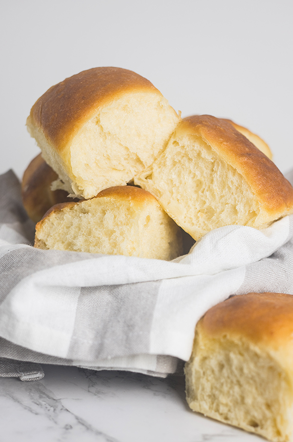 Easy potato rolls, freshly baked and piled into a towel-lined bowl.