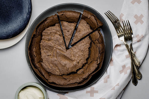 A whole flourless chocolate cake with two wedges cut out, on a grey plate with pink patterned kitchen towel and forks to the side.