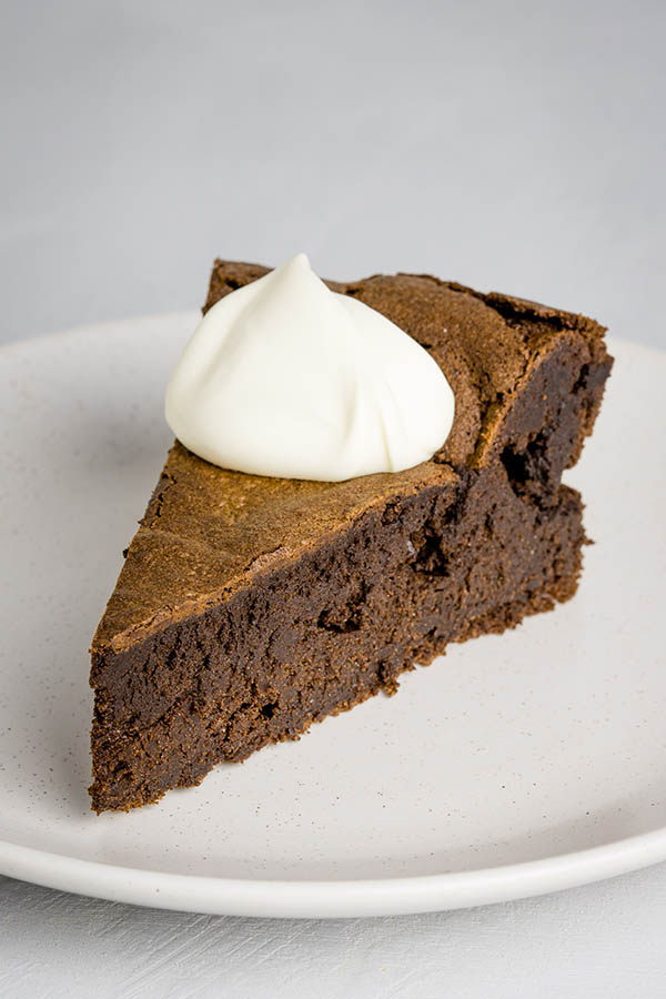 A wedge of flourless chocolate cake on a neutral speckled plate, adorned with a dollop of thick cream.