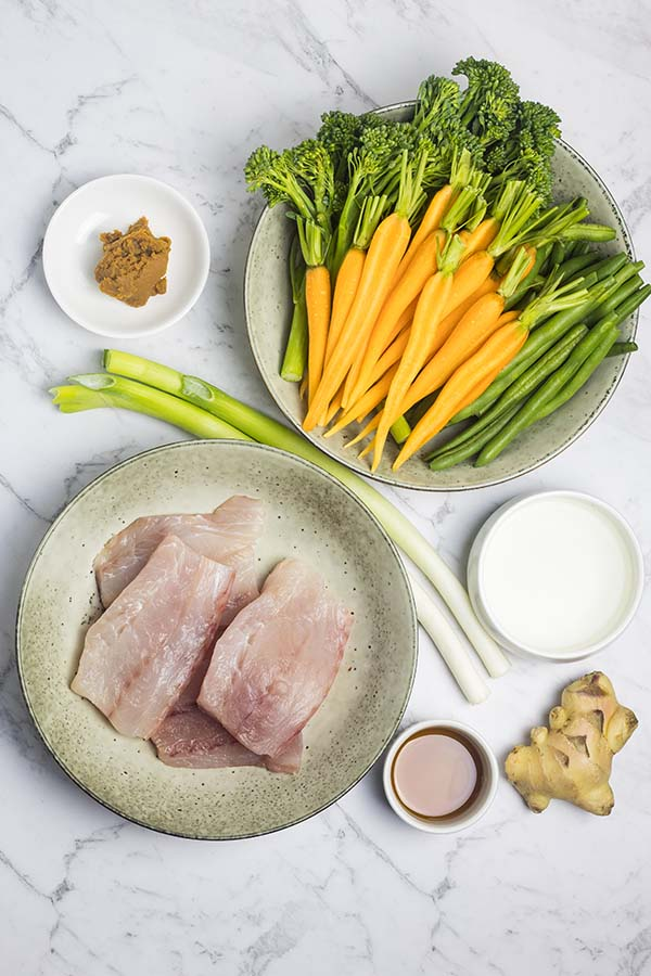 Ingredients laid out to make easy steamed fish parcels with miso ginger dressing.