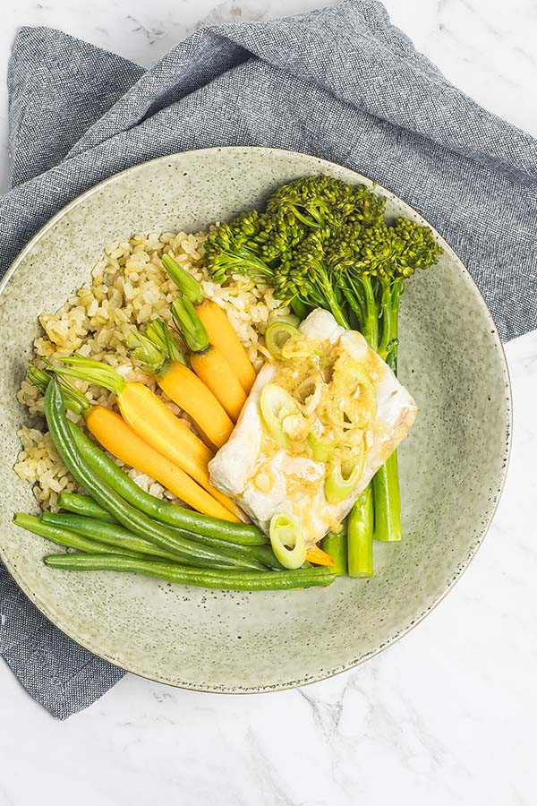 Easy fish parcels with carrots, beans and broccoli, served on brown rice with miso ginger dressing over the top.