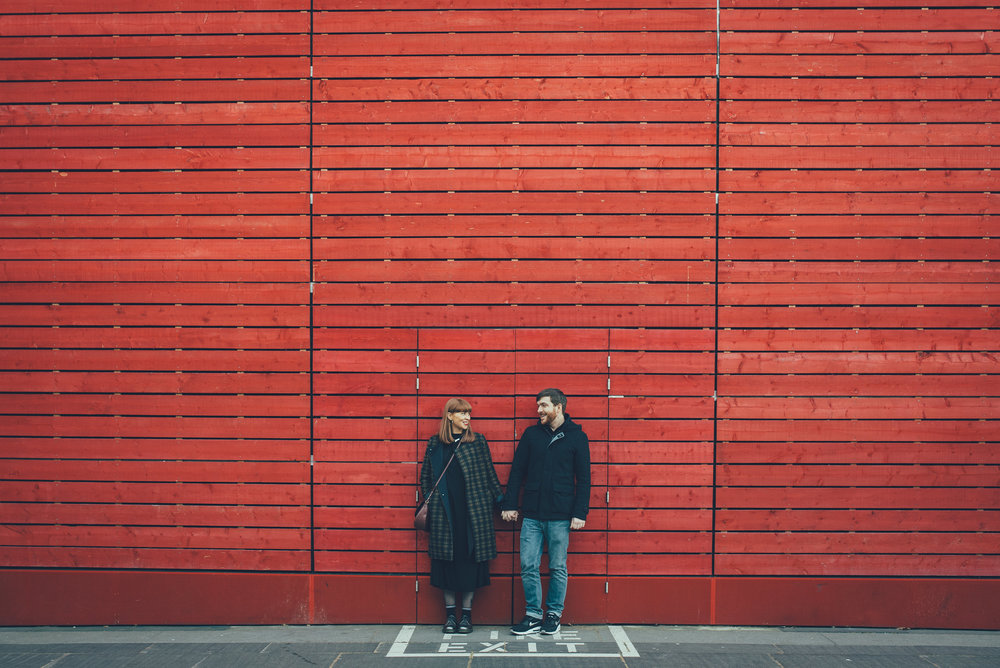 Couple in front of red wall at the National Theatre London