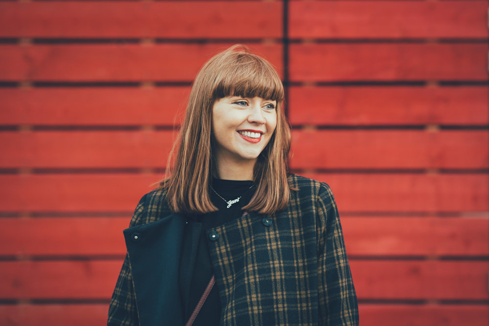Redhead smiling in front of red wall at the National Theatre London