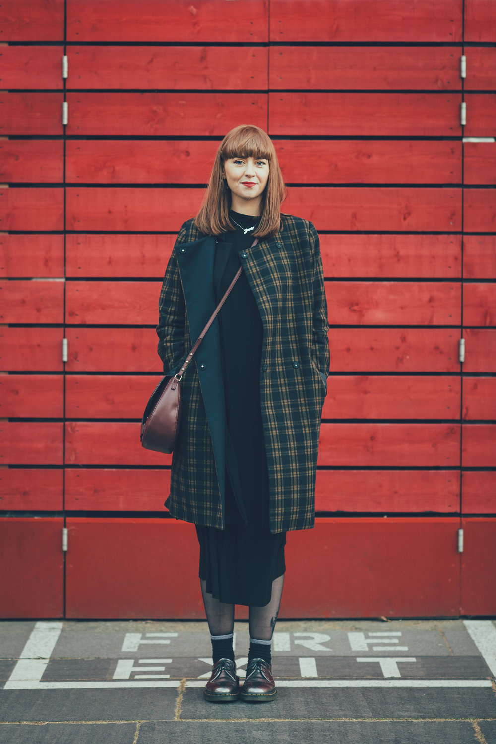 Redhead standing in front of red wall at the National Theatre London