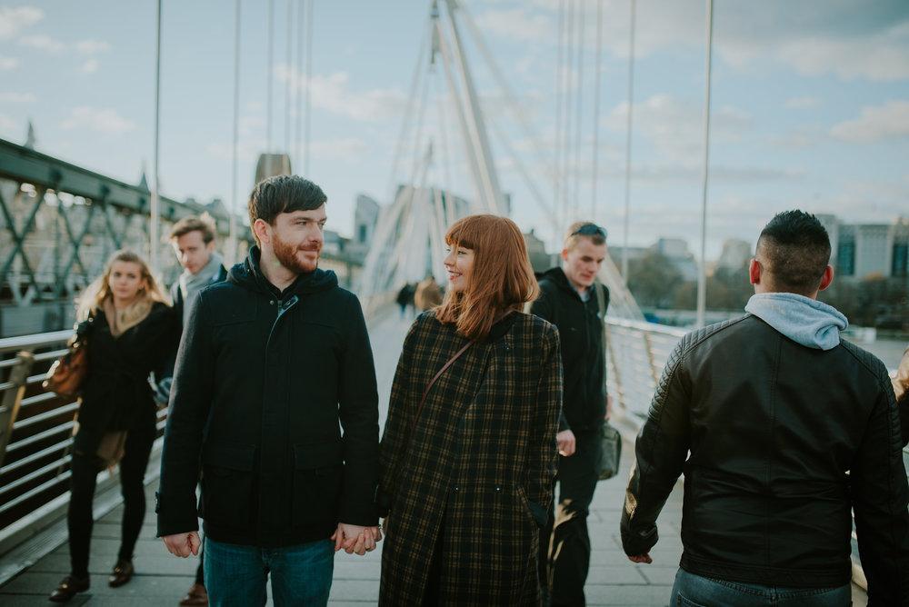 Couple walking along Embankment Bridge London