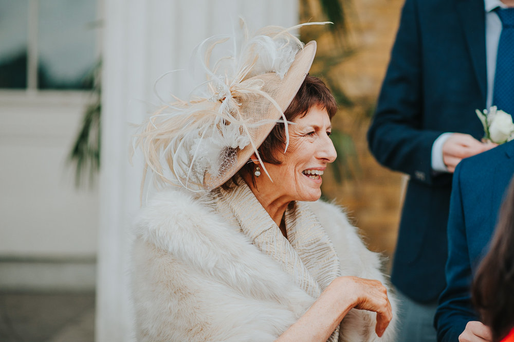 Mother of the groom wearing wedding hat outside Clissold House London