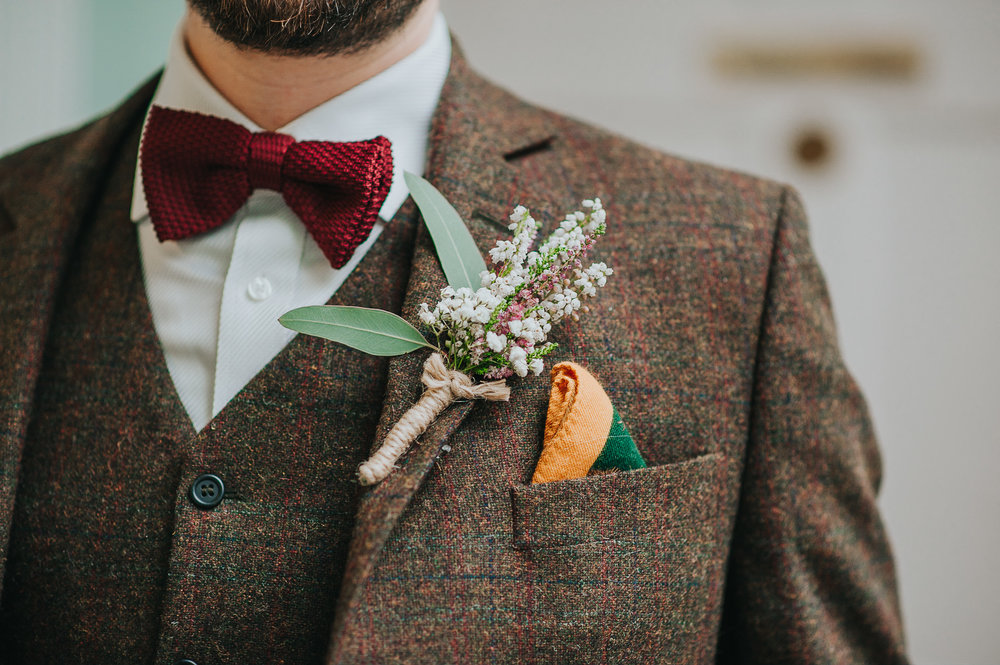 Detail of groom's tweed wedding suit with flower buttonhole at Clissold House London