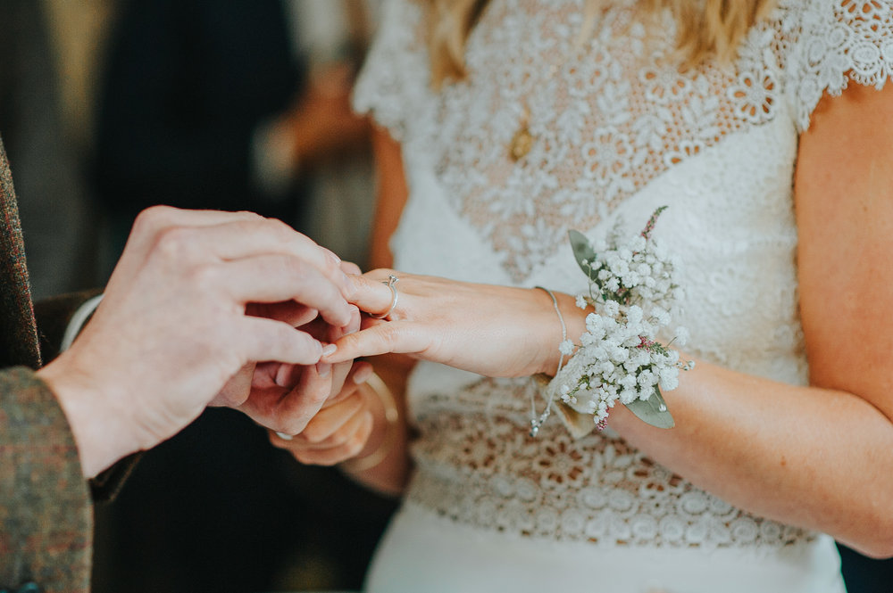 Bride and groom exchange wedding rings at ceremony at Clissold house London