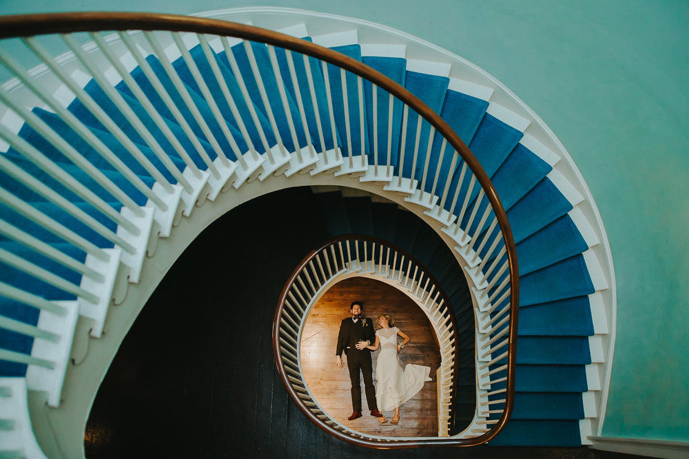 Creative alternative wedding photography of bride and groom and staircase at Clissold house London