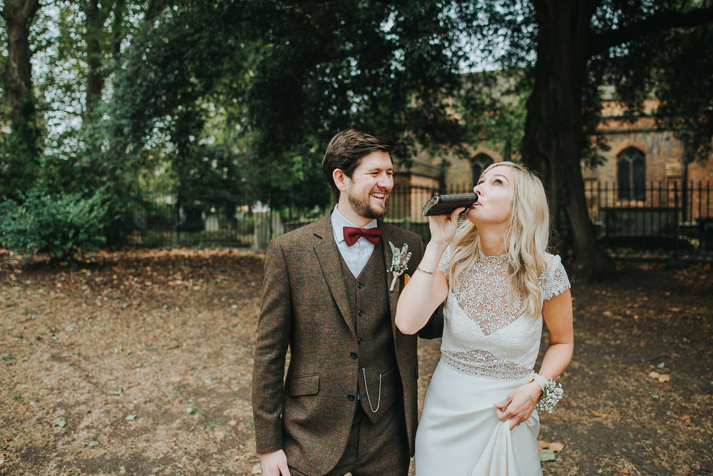 Bride and groom drinking whiskey from hip flask in Clissold Park on their wedding day