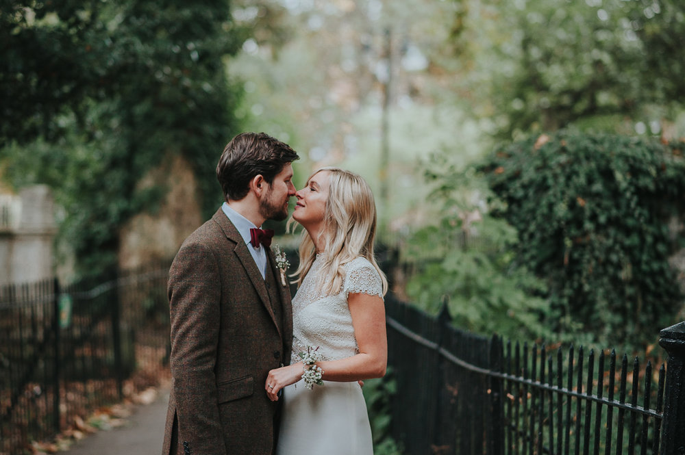 Bride and groom kissing in Clissold Park after wedding ceremony