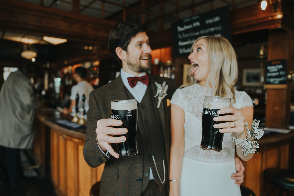 Bride and groom drink pints of Guinness in London pub The Rose and Crown after wedding