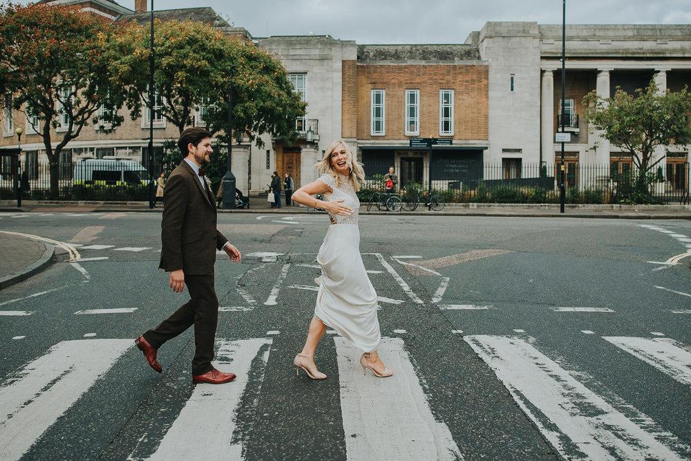 Bride and groom walking across zebra crossing after wedding Beatles Abbey Road style