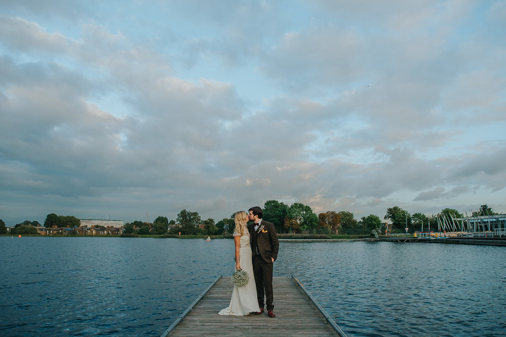 Bride and groom at wedding reception kissing on jetty at Stoke Newington West Reservoir Centre at sunset