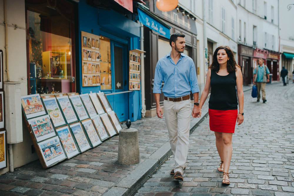Couple in love walking down a pretty Montmartre street with shops