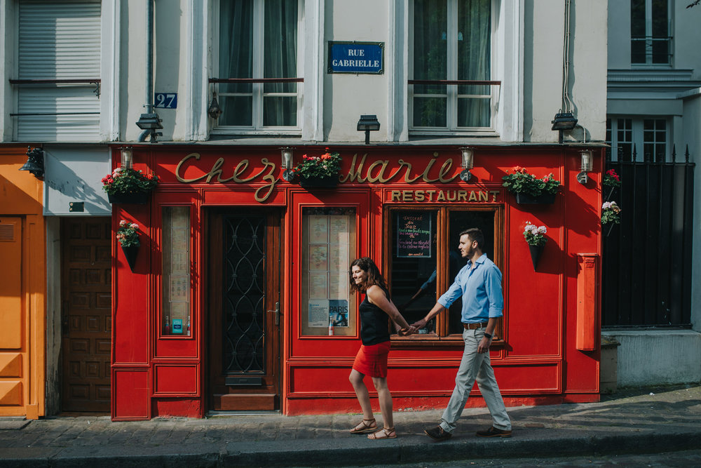 Engagement photoshoot couple in love walking by red Paris cafe on Montmartre street