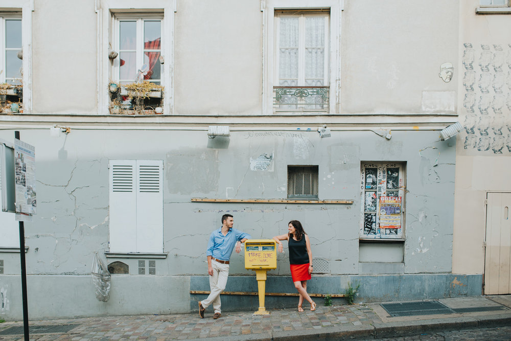 Paris engagement photography couple in love standing next to make love not war sign