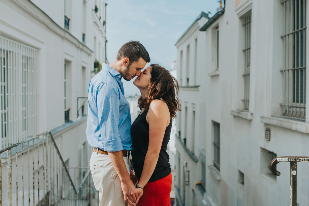French couple shoot man and woman kissing in front of Parisian architecture in Montmartre