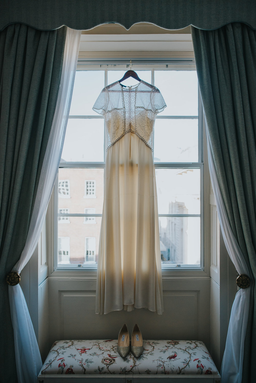 Burberry wedding dress hanging up in window of Merrion Hotel Dublin