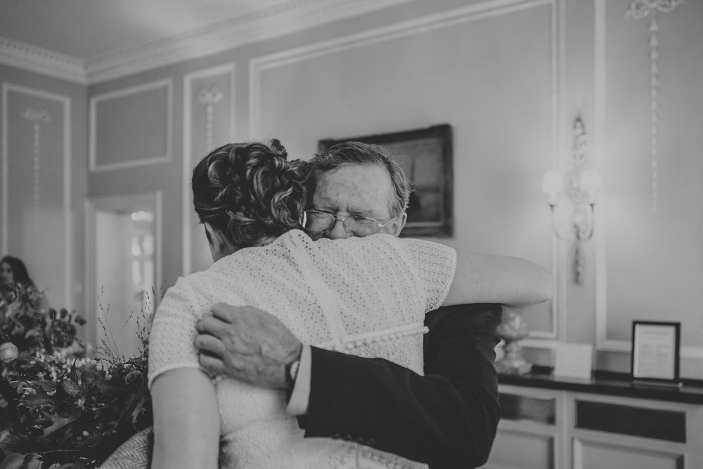 Bride being hugged by father on wedding day