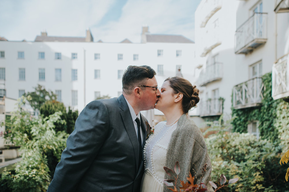 Bride and groom having their first kiss on their wedding day