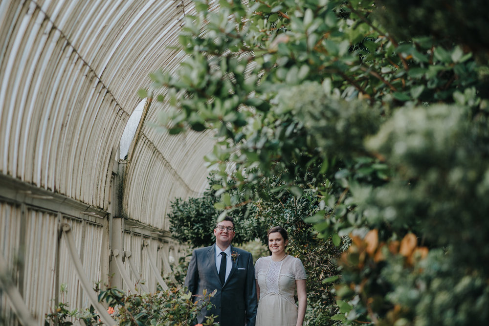 Bride and groom standing among the plants in greenhouse at Botanic Gardens Dublin on their wedding day