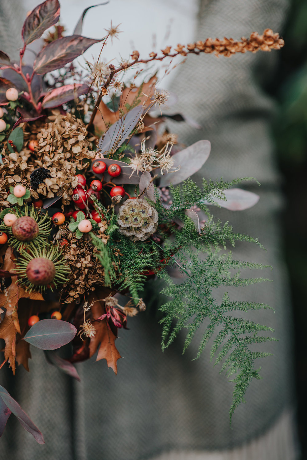 Close up of autumn bouquet with flowers, leaves and berries