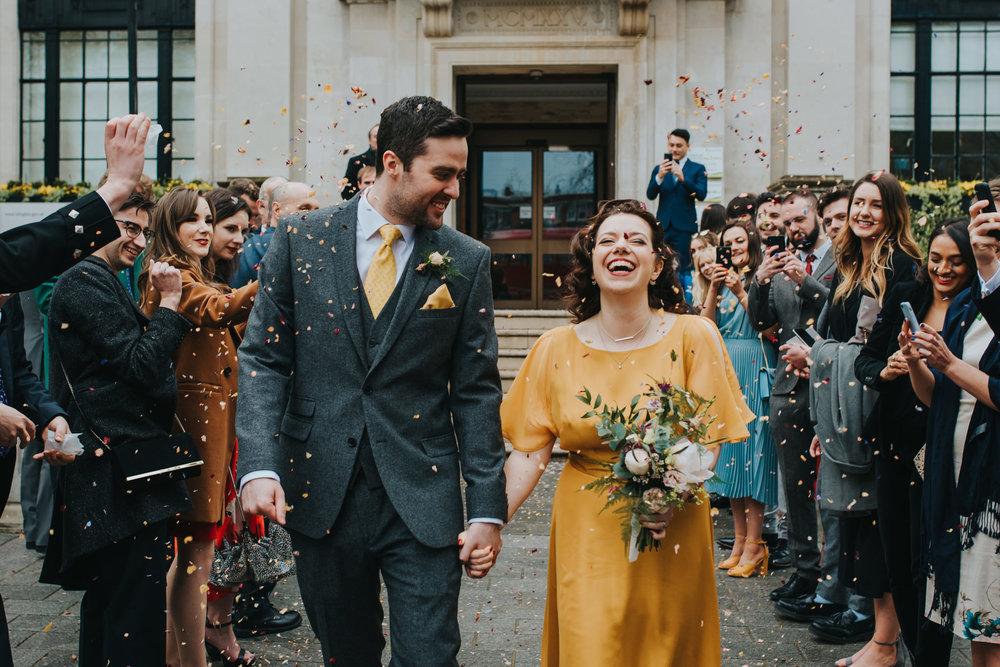 Bride and groom smiling confetti shot