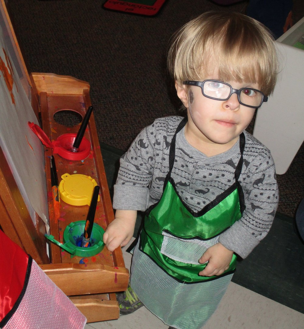 TLC preschooler Oliver paints in Ms. Jen's classroom.