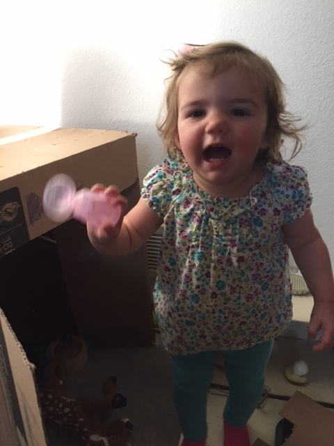 TLC student Daphne has fun with a combination of toys and cardboard boxes at home.