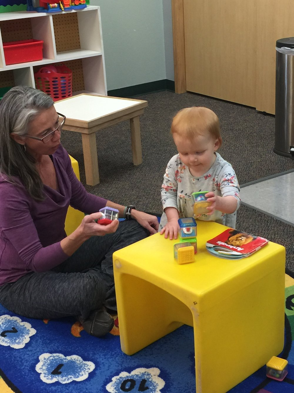 Kathy plays with a toddler during class.