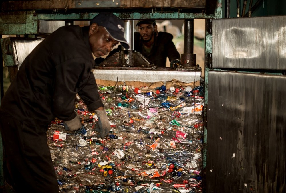 Phillip Julius (front) and another Cannibal Recycling employee prepare to process post-consumer PET plastic bottles. Image © PETCO