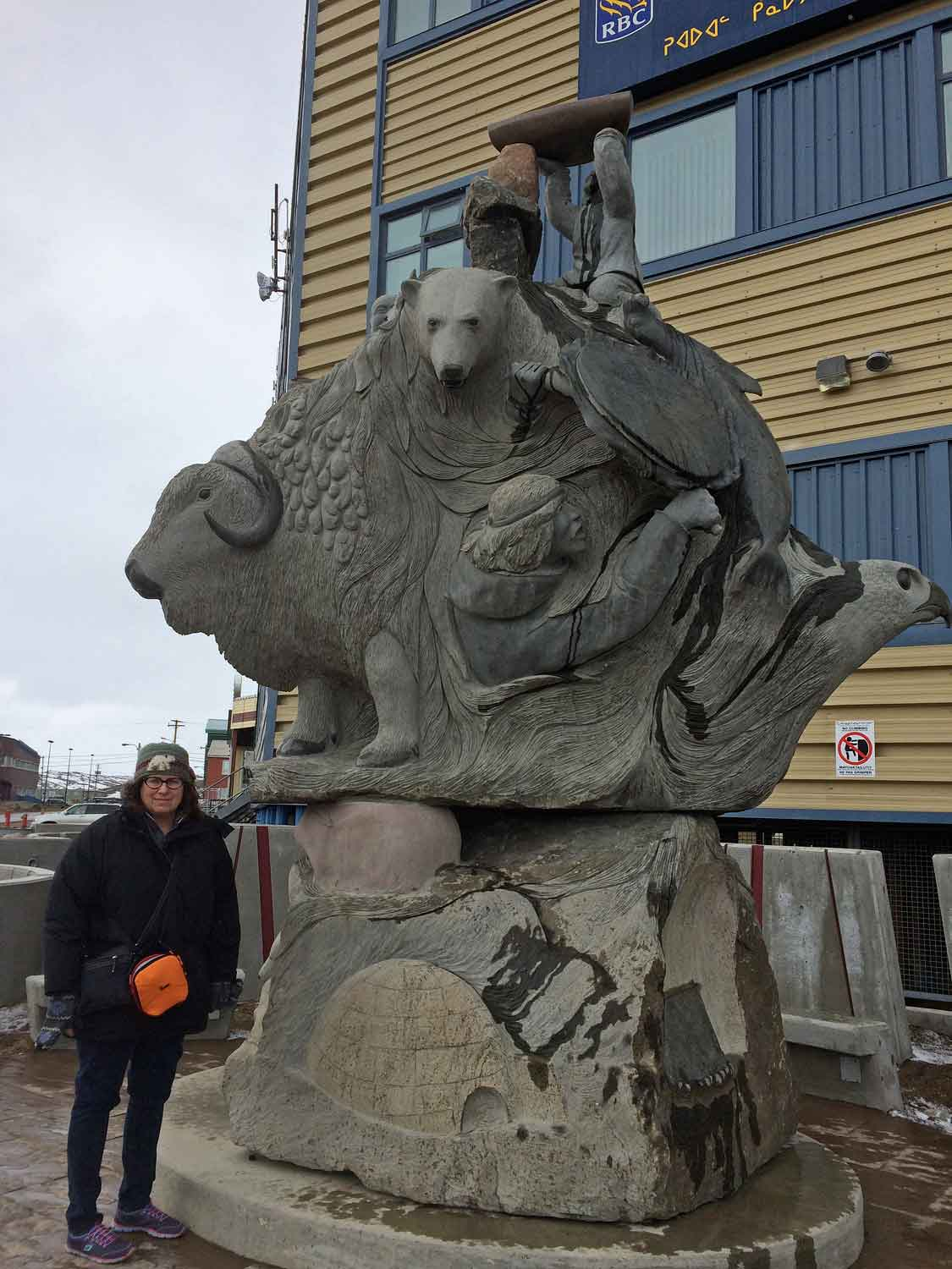 Me, looking self conscious, but spiffy in my newly gifted hat  (made by a textile artist  from Pangnirtung). In front of public sculpture. Created co-operatively by multiple carvers.