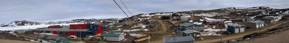 ©Christine-Montague_Cape-Dorset-school-bus. Sadly, for the community, the red and blue high school seen on the left, burnt down.