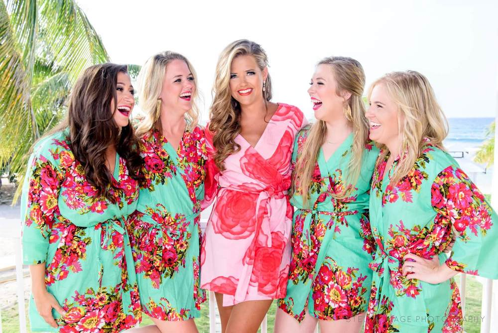 Bridesmaids laugh with each other in vibrant robes on balcony in Jamaica