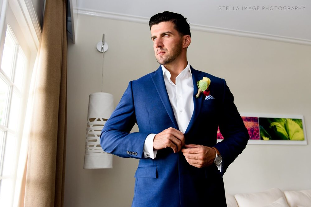 Handsome groom buttons jacket and looks out window at Melia Braco Village Jamaica.