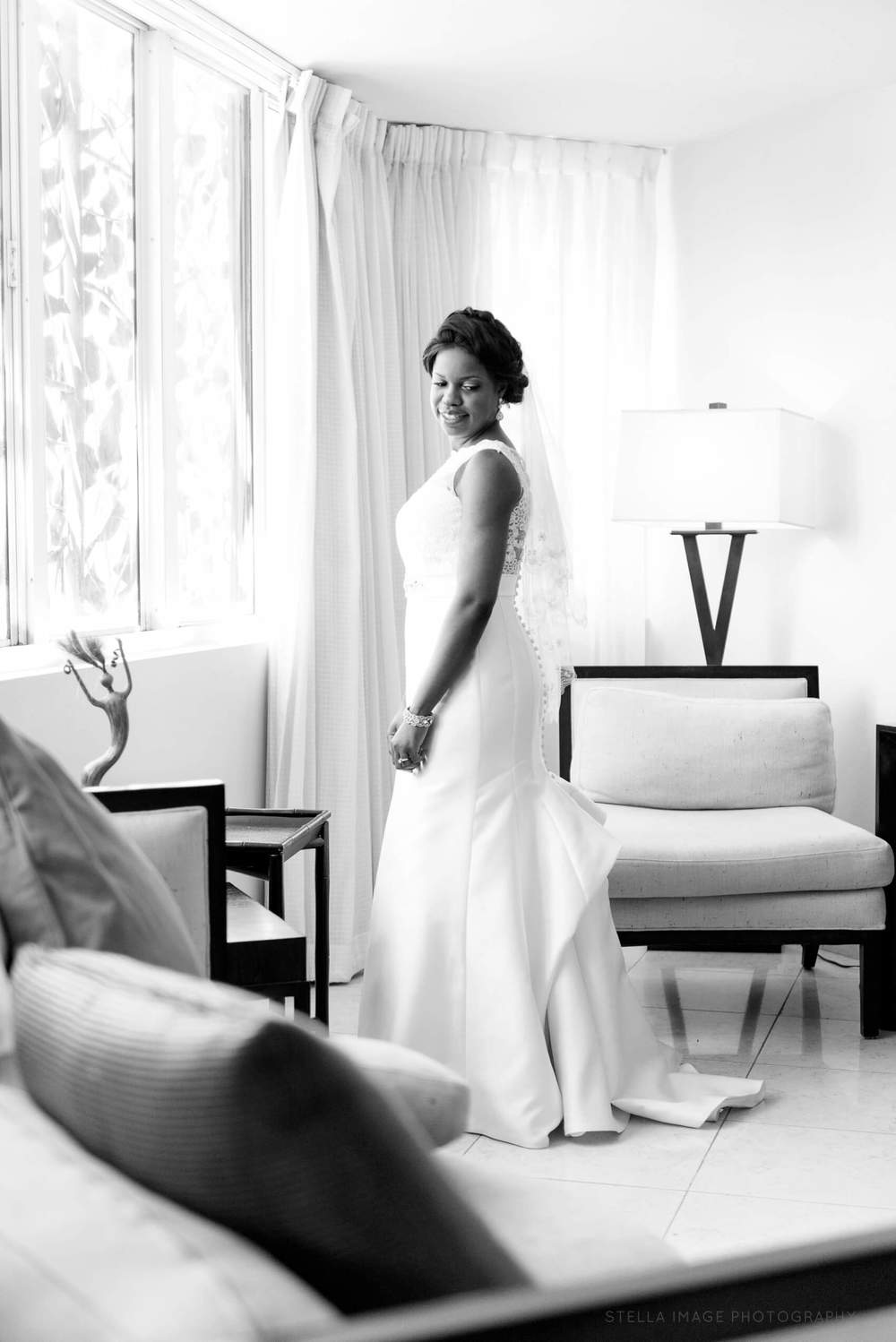 Bride poses in front of window in wedding gown at the Mutiny hotel in Coral Gables, Miami.