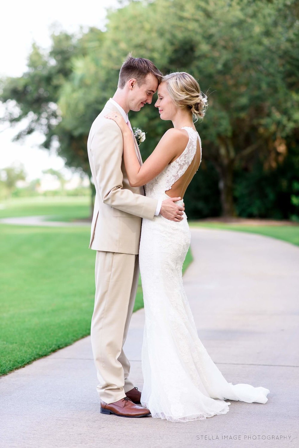 Bride and groom share a hug on the golf course at mayacoo lakes country club after wedding.