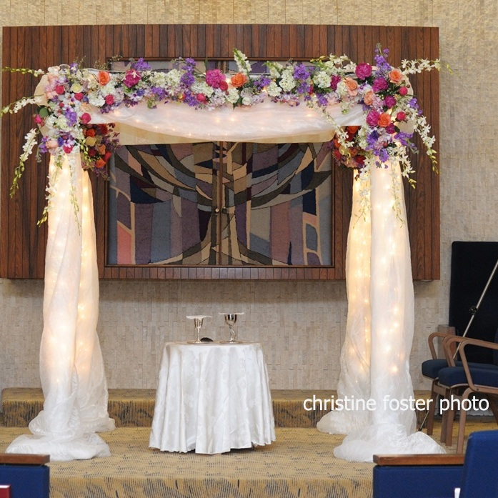 Chuppah - Fabric Pole Chuppah with Substantial Flowers, String Lights Throughout, and Medium Fabric (1,500)