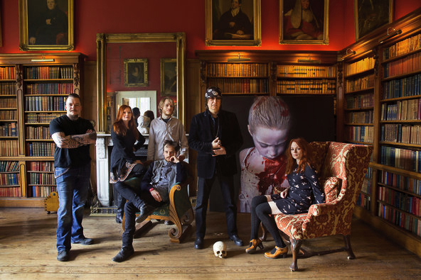 "The artist Gottfried Helnwein with his wife, Renate, and their four children, from left, Cyril, Wolfgang Amadeus, Ali (sitting) and Mercedes in the library of the 19th-century Gurteen Castle. In the background, a painting from Gottfried's ""The Disasters of War"" series 2014, Kenneth O Halloran"
