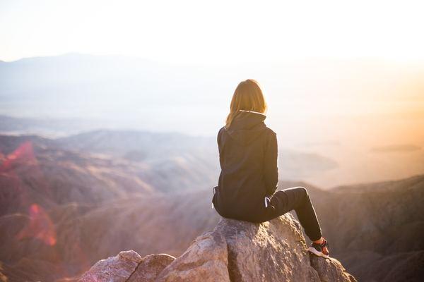 https://freedesignfile.com/404119-woman-sitting-on-the-peak-watching-the-sunrise-stock-photo/